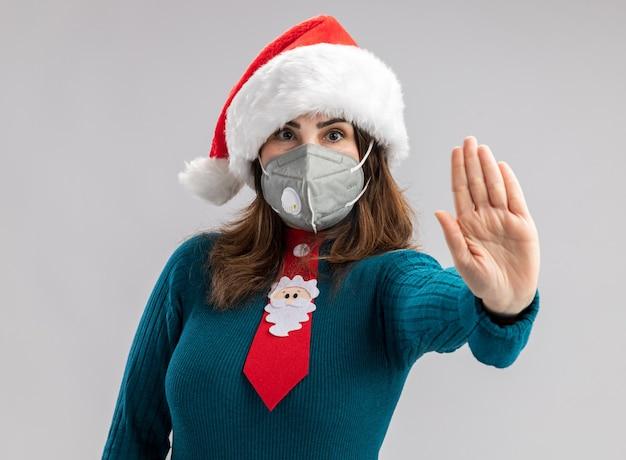 Zuversichtlich erwachsene kaukasische frau mit santa hut und santa krawatte, die medizinische maske trägt, die stopphandzeichen gestikuliert Kostenlose Fotos