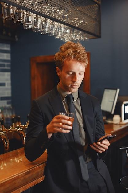 Zuversichtlich fröhlicher mann, der am bartheke sitzt, bier trinkt und auf smartphone vernetzt. Kostenlose Fotos