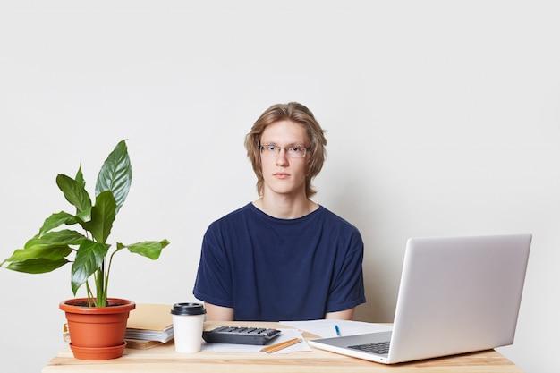 Zuversichtlich geschäftsmann erstellt jahresbericht, berechnet zahlen, verwendet moderne laptop-computer und taschenrechner, trinkt kaffee zum mitnehmen, schaut ernsthaft in die kamera, isoliert über weiße wand Kostenlose Fotos