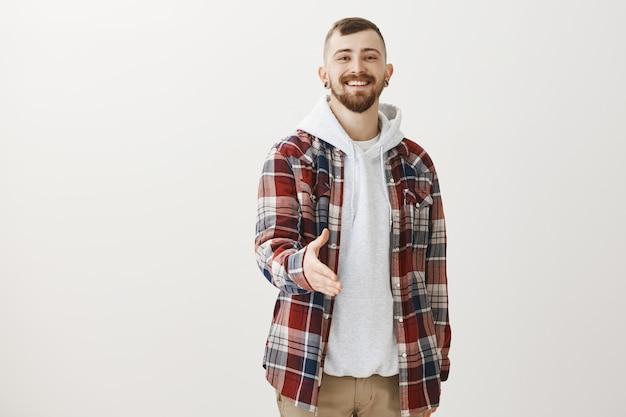 Zuversichtlich glücklicher hipster strecken hand zum händedruck aus und begrüßen jemanden Kostenlose Fotos