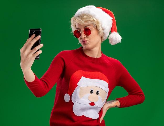 Zuversichtlich junge blonde frau, die weihnachtsmütze und weihnachtsmann-weihnachtspullover mit brille trägt, die hand auf taille hält, die selfie mit gespitzten lippen lokalisiert auf grünem hintergrund nimmt Kostenlose Fotos