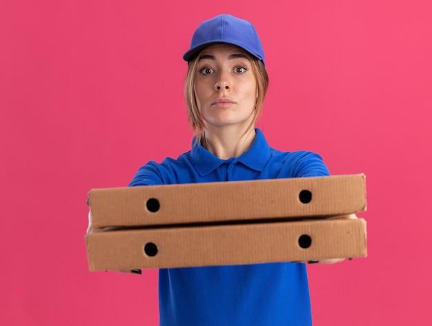 Zuversichtlich junge hübsche lieferfrau in uniform hält pizzaschachteln isoliert Kostenlose Fotos