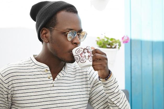 Zuversichtlich junger afroamerikanischer männlicher student gekleidet, der stilvoll kaffee am college-café genießt. trendig aussehender dunkelhäutiger mann mit becher, der tee trinkt, während er allein im gemütlichen restaurant zu mittag isst Kostenlose Fotos