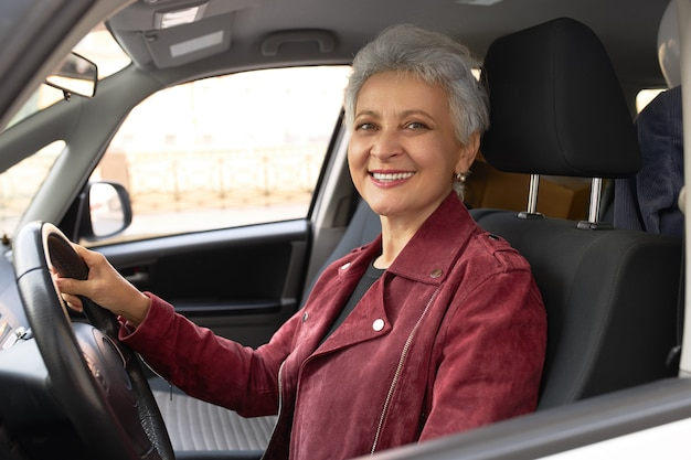 Zuversichtlich reife geschäftsfrau in der stilvollen jacke, die auto auf stadtstraßen fährt Kostenlose Fotos