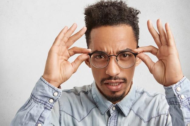 Zuversichtlich streng ernst mann schaut gründlich durch runde brille, versucht etwas zu sehen Kostenlose Fotos