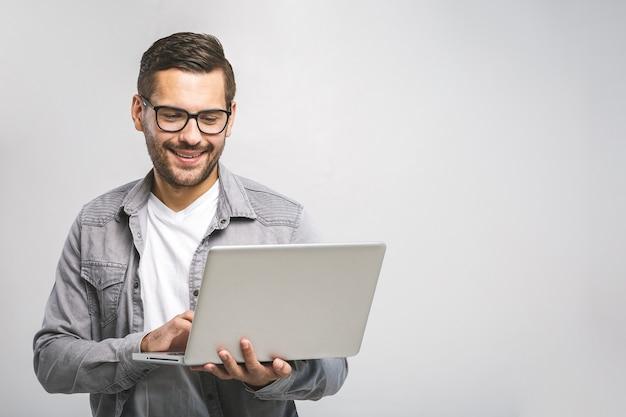 Zuversichtlicher geschäftsexperte. zuversichtlich junger schöner mann im hemd, das laptop hält und lächelt, während gegen weißen hintergrund stehend Premium Fotos