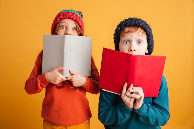Zwei ängstliche kleine rothaarige kinder, die gesichter mit büchern bedecken. Kostenlose Fotos
