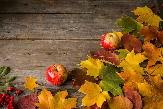 Zwei äpfel und herbstlaub auf hölzernem hintergrund Premium Fotos