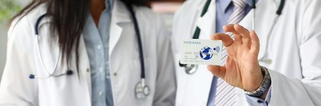 Zwei ärzte zeigen plastikkarte Premium Fotos