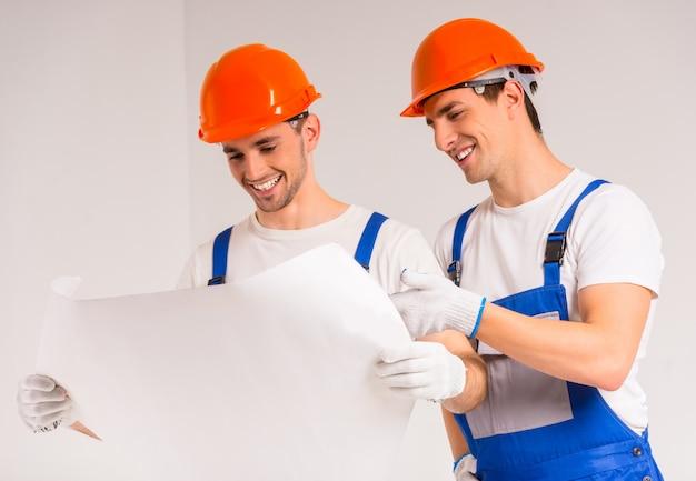 Zwei arbeiter stehen und schauen sich den plan an. Premium Fotos