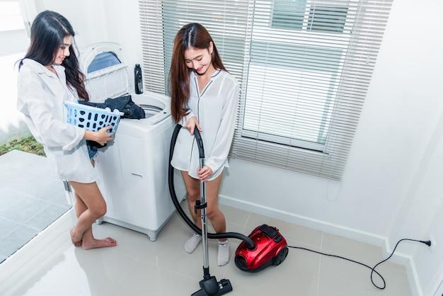 Zwei asiatinnen, die hausarbeit und aufgaben in der küche tun. Premium Fotos