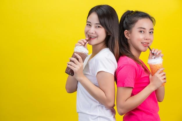 Zwei asiatische frauen, die gefrorenen milchtee und gefrorenen kakao auf einem gelb trinken. Kostenlose Fotos