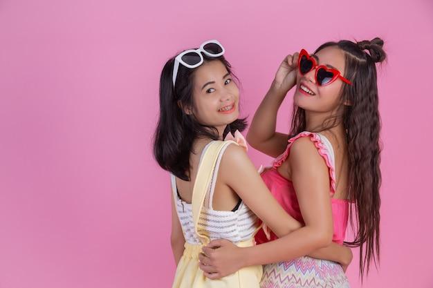 Zwei asiatische mädchen, die freunde sind, sind glücklich und haben ein rosa. Kostenlose Fotos