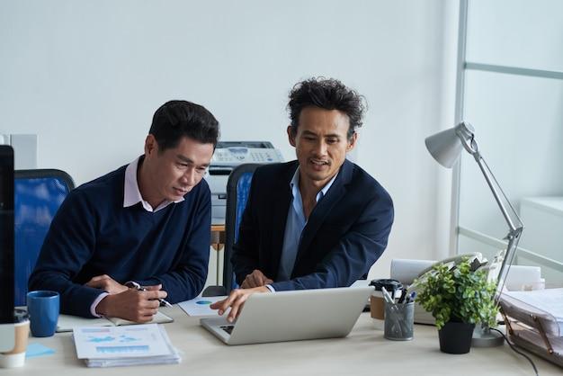 Zwei asiatische männliche kollegen, die zusammen im büro sitzen und laptopschirm betrachten Kostenlose Fotos