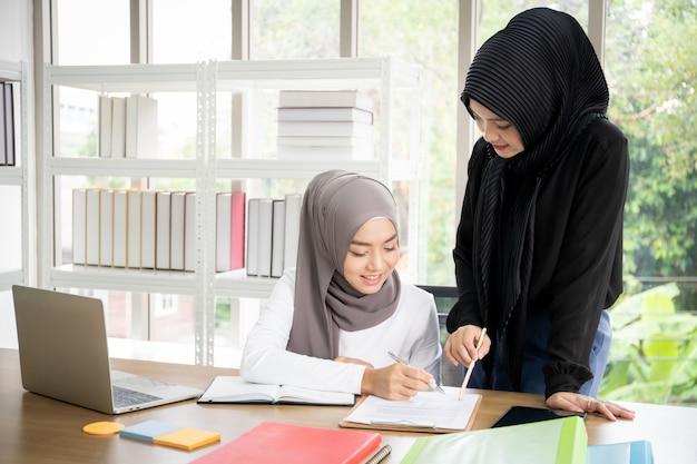 Zwei asiatische muslimische geschäftsfrauen sprechen und arbeiten im büro zusammen Premium Fotos