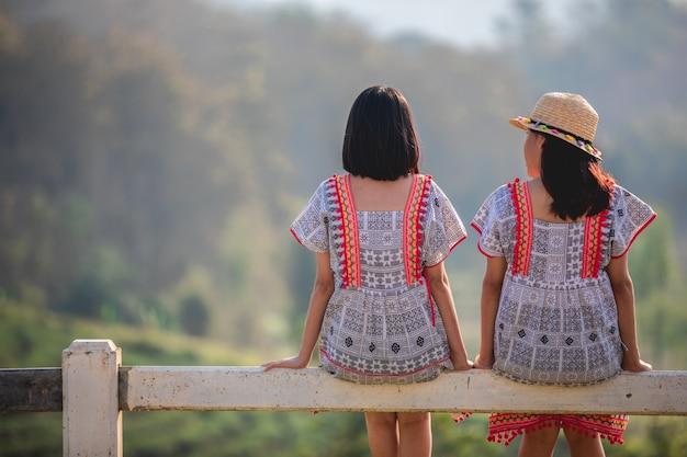 Zwei asiatische nette und junge mädchen, die auf dem gartenzaun auf sonnenuntergang sitzen Premium Fotos