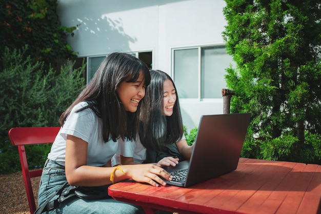 Zwei asiatische teenager tippen auf computer labtop glück emotion Premium Fotos