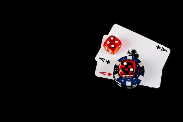Zwei asse spielkarten mit würfeln und pokerchips auf schwarzem hintergrund Kostenlose Fotos