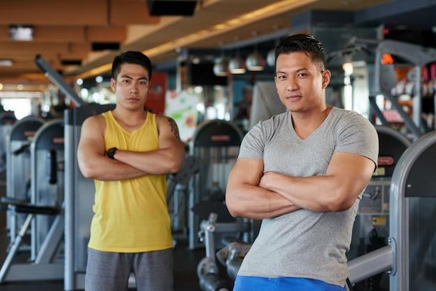 Zwei athletische asiatische männer mit den gekreuzten armen, die in der turnhalle aufwerfen Kostenlose Fotos