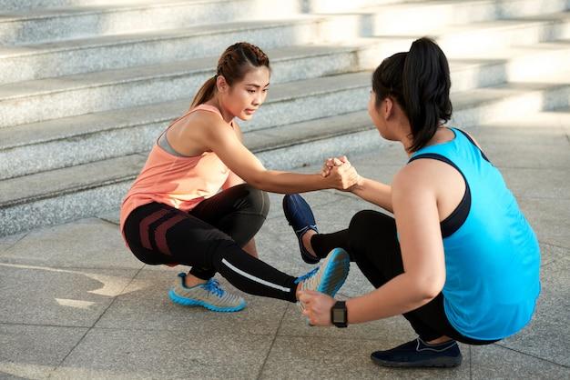 Zwei athletische freundinnen, die das händchenhalten der einzelnen fahrwerkbeinhocke tun Kostenlose Fotos