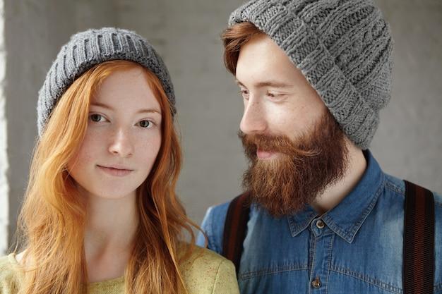 Zwei attraktive freunde, die drinnen graue hüte tragen. glücklicher schöner mann mit stilvollem bart, der mit liebevollem und fürsorglichem ausdruck seine freundin mit langen roten haaren ansieht. Kostenlose Fotos