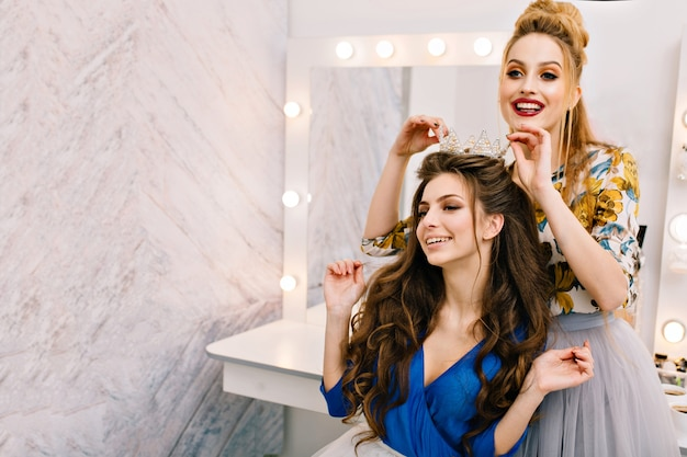 Zwei attraktive fröhliche modelle mit stilvollem look, die spaß im schönheitssalon haben Kostenlose Fotos
