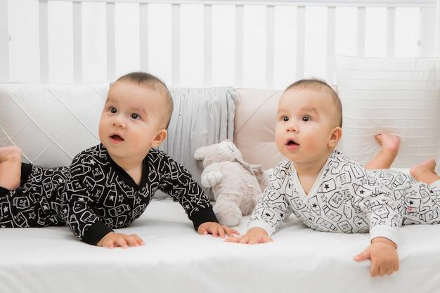 Zwei babys im bett auf grau Premium Fotos
