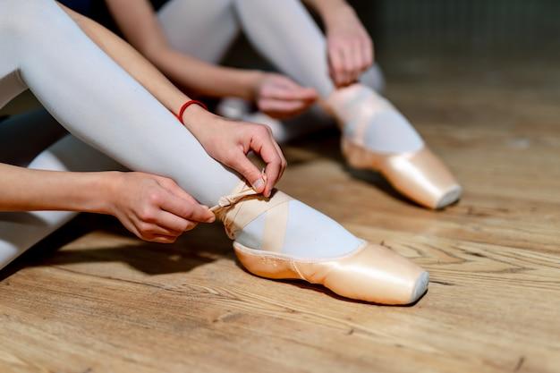 Zwei ballettmädchen, die auf ihre spitzenschuhe sitzen auf dem bretterboden sich setzen. balletttänzer, die ballettschuhe binden. nahansicht Premium Fotos