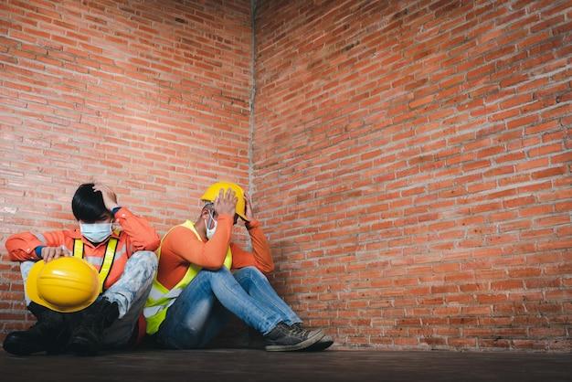 Zwei bauarbeiter bedauern es, traurig auf der baustelle zu sitzen. das tragen einer medizinischen maske, um covid-19 zu verhindern, ist arbeitslosigkeit und die wirtschaftskrise. arbeitslosigkeit während covid-19 fehlgeschlagen Premium Fotos