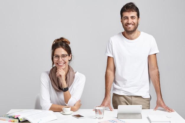 Zwei beste freunde mit fröhlichen ausdrücken arbeiten im modernen büro zusammen und machen ein zukünftiges projekt Kostenlose Fotos