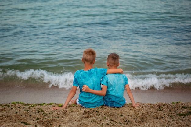 Zwei brüder, die auf seestrand am sommertag sitzen. Premium Fotos