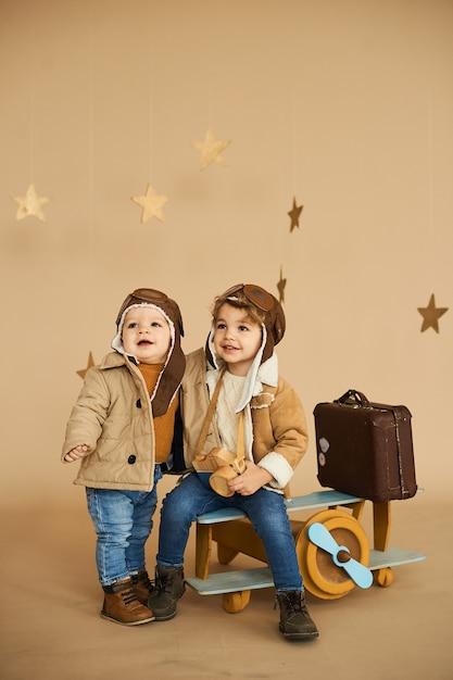 Zwei brüder werden mit einem spielzeugflugzeug und einem koffer auf beigem hintergrund gespielt Premium Fotos