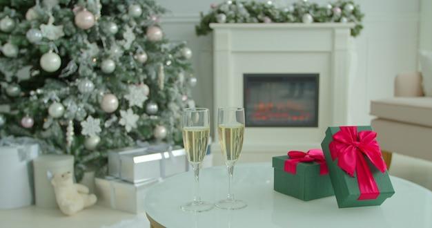 Zwei champagnergläser auf tisch am heiligabend mit weihnachtsbaum und deko im hintergrund. Premium Fotos