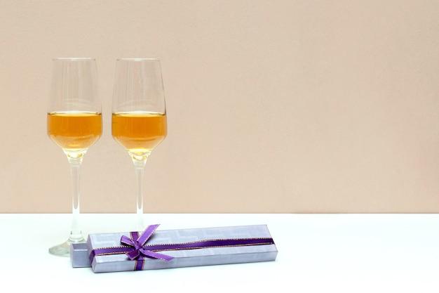 Zwei champagnergläser und geschenkbox am valentinstag, weiß mit kopienraum, liebeskonzept. Premium Fotos