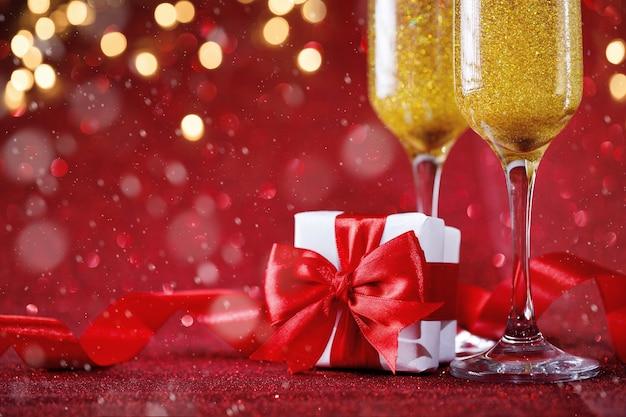Zwei champagnergläser und geschenkbox auf rotem glitzerhintergrund Premium Fotos