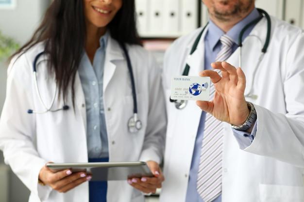 Zwei doktoren, die in camera plastikkarte zeigen Premium Fotos