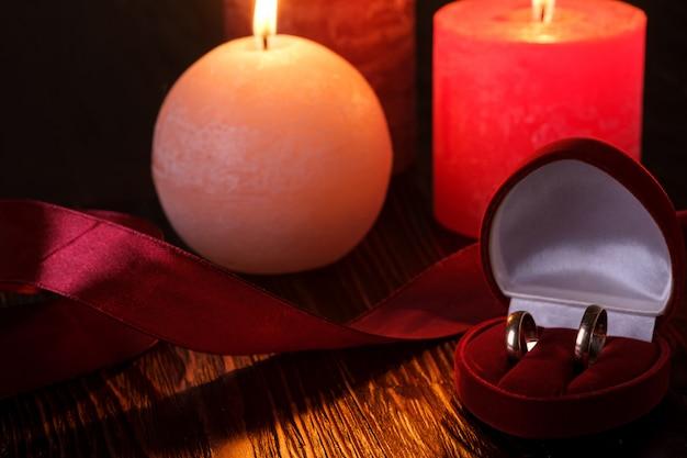 Zwei eheringe in der roten geschenkbox mit kerzenlicht mit drei wachsflammen mit band im dunklen romantischen licht, liebesdatierung, valentinstag, selektiver fokus Premium Fotos