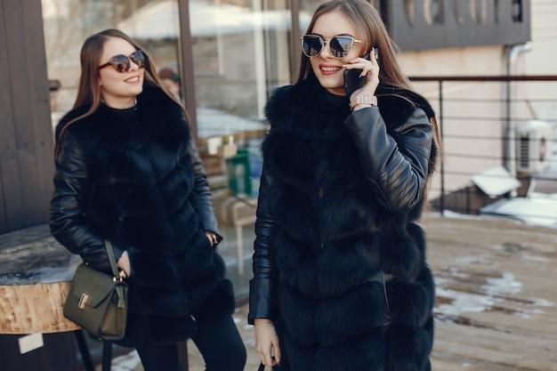 Zwei elegante und stilvolle mädchen, die in einer winterstadt stehen und das telefon verwenden Premium Fotos