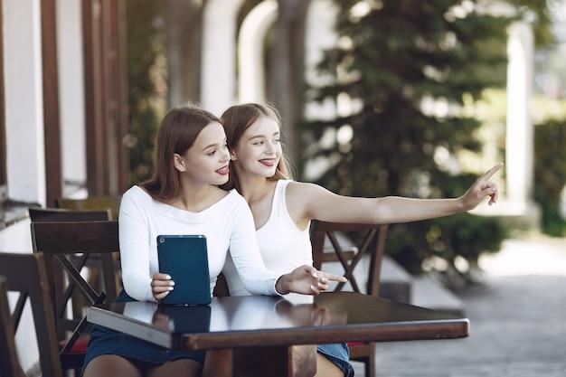 Zwei elegante und stilvolle mädchen in einem sommercafé Kostenlose Fotos