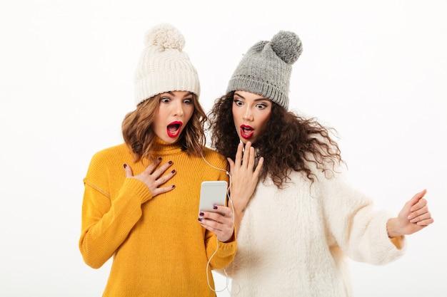 Zwei entsetzte mädchen in den strickjacken und in hüten, die zusammen bei der anwendung des smartphone über weißer wand stehen Kostenlose Fotos