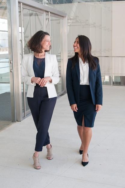 Zwei entspannte weibliche kollegen, die in bürohalle gehen Kostenlose Fotos