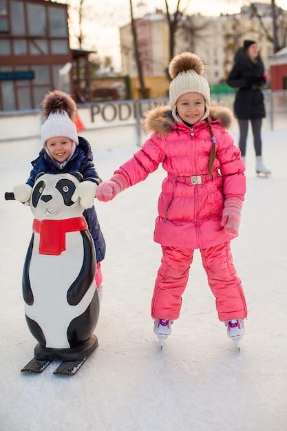 Zwei entzückende kleine mädchen, die an der eisbahn eislaufen Premium Fotos
