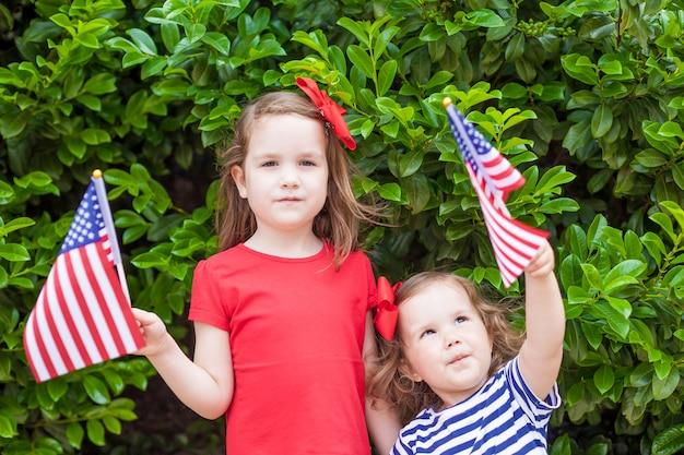 Zwei entzückende kleine schwestern, die draußen amerikanische flaggen am schönen sommertag halten Premium Fotos