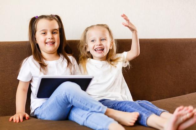 Zwei entzückende kleine schwestern, die zu hause mit einer digitalen lächelnden schwester der tablette mit tabletten-pc-computer spielen Premium Fotos