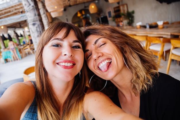 Zwei europäische kaukasische freundinnen mit natürlichem make-up und kurzen haaren machen selfie im sommercafé Kostenlose Fotos