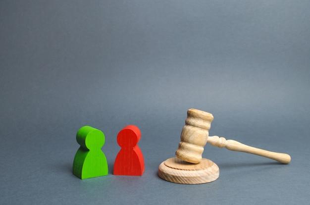 Zwei figuren von personengegnern stehen in der nähe des richters. konfliktlösung vor gericht Premium Fotos
