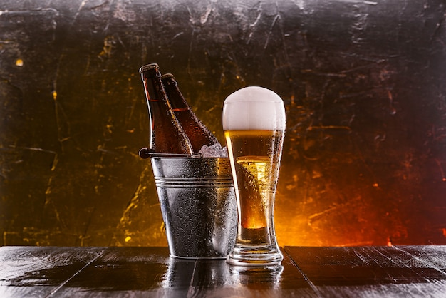 Zwei flaschen bier in einem eimer mit eis und ein glas bier mit üppigem schaum Premium Fotos