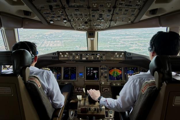 Zwei flugzeugpiloten steuern das flugzeug in richtung der landebahn. Premium Fotos
