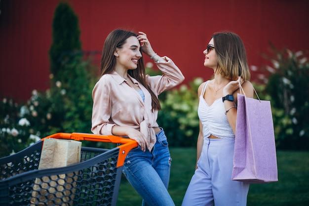 Zwei frauen, die durch den markt mit einkaufswagen kaufen Kostenlose Fotos