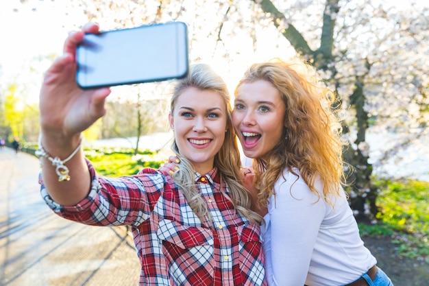 Zwei frauen, die ein selfie am park in london nehmen Premium Fotos
